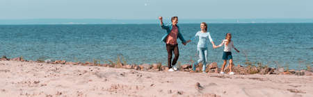 Panoramic shot of family with daughter holding hands while walking on beach