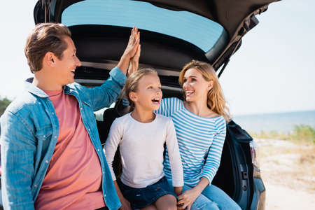Selective focus of parents giving high five near daughter and car on beach