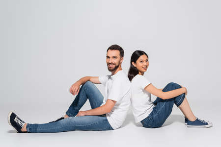young asian woman and bearded man in white t-shirts and jeans sitting on white and looking at camera