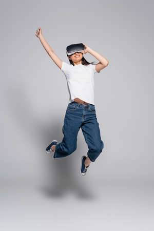 young asian woman in white t-shirt, jeans and gumshoes jumping with raised hand while using vr headset on gray