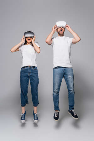 excited couple in jeans and white t-shirts levitating with open mouths while using vr headsets on gray