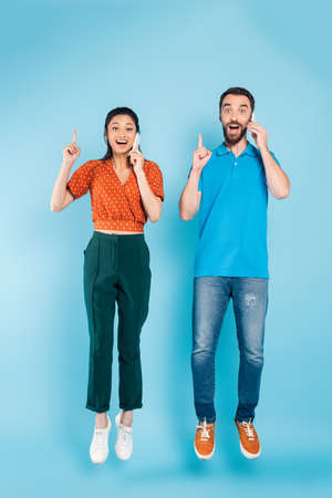 excited interracial couple talking on smartphones and showing idea sign while levitating on blue