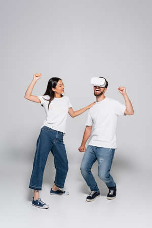 asian woman in jeans and white t-shirt touching shoulder of excited man dancing and singing in vr headset on gray