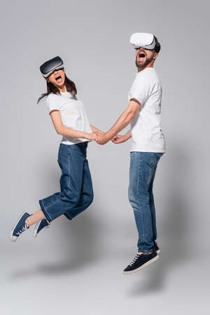 excited couple in vr headsets, jeans and white t-shirts holding hands while levitating on gray