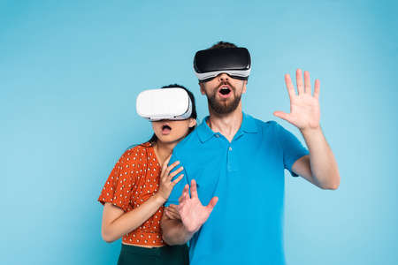 scared woman in red blouse touching excited man in polo t-shirt while using vr headsets together isolated on blue
