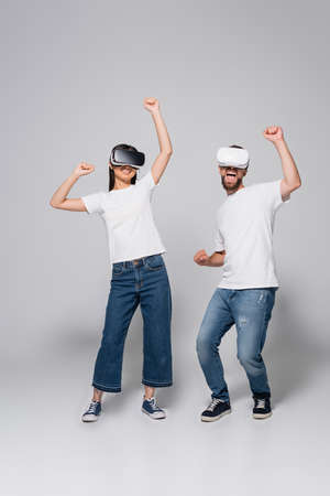 excited couple in jeans, gumshoes and white t-shirts dancing while using vr headsets on gray