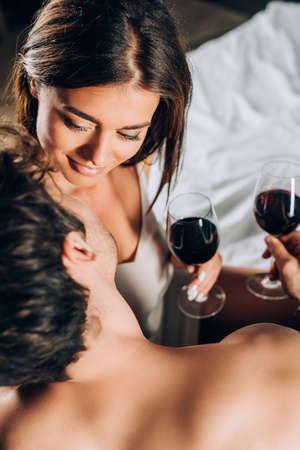 Overhead view of shirtless man holding glass of wine near young girlfriend on bed