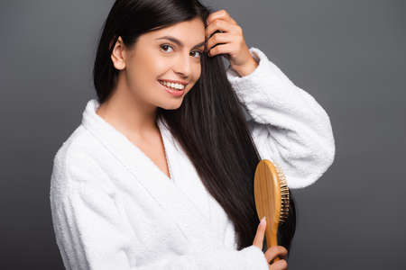 brunette woman in bathrobe brushing hair and smiling isolated on black