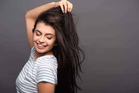 side view of brunette woman with closed eyes smiling and touching hair isolated on black Stock fotó - 154911216