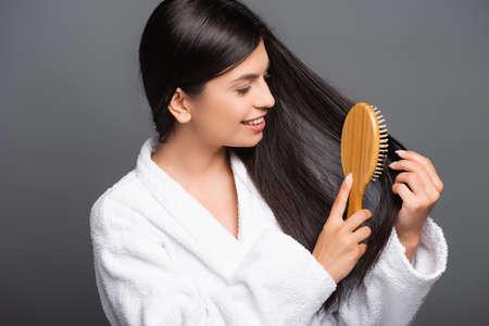 brunette woman in bathrobe brushing hair and smiling isolated on black Stock fotó - 154911225