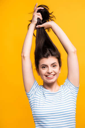 brunette woman holding hair above head and smiling isolated on yellow Stock fotó - 154911231