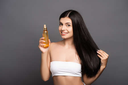 brunette woman holding hair oil in spray bottle and smiling isolated on black