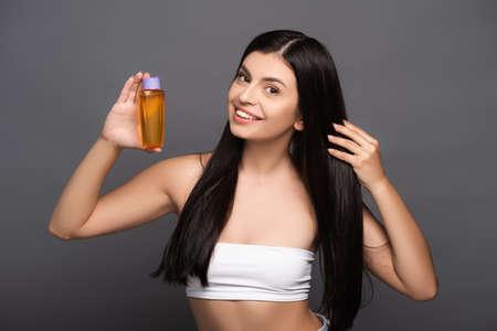 brunette woman holding hair oil in bottle isolated on black Stock fotó - 154911250