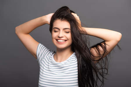 brunette woman with closed eyes smiling and touching hair isolated on black Stock fotó - 154911252