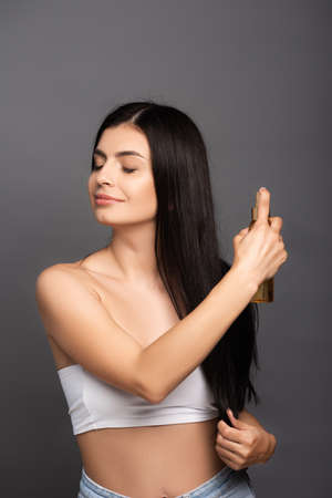 brunette woman spraying oil on hair isolated on black