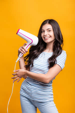 brunette woman with curls holding hairdryer isolated on yellow