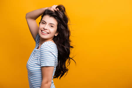 side view of brunette woman toughing curly long hair and smiling isolated on yellow