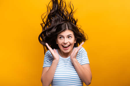 brunette long haired woman with curls jumping and smiling isolated on yellow Stock fotó