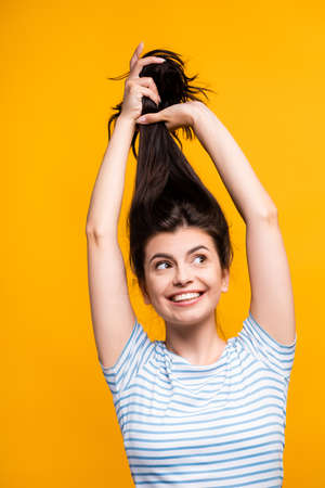 brunette woman holding hair above head and smiling isolated on yellow