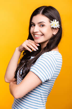 brunette young woman with flowers in hair smiling isolated on yellow