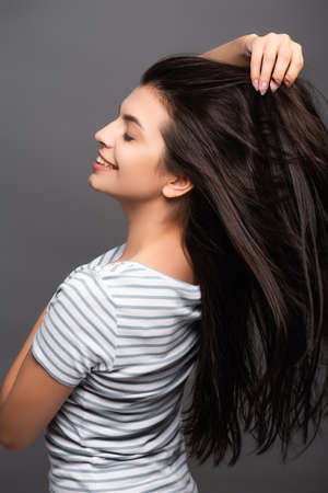 side view of brunette woman with closed eyes smiling and touching hair isolated on black