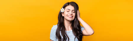 brunette young woman with flowers in hair and closed eyes smiling isolated on yellow, panoramic shot Stock fotó - 154911324