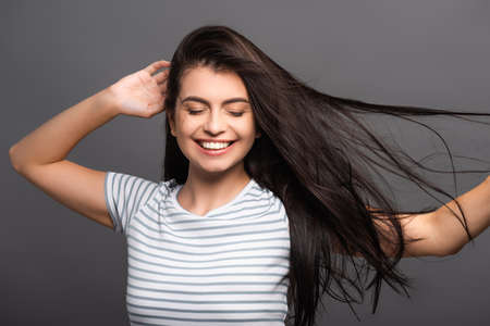 brunette woman with closed eyes smiling and touching hair isolated on black Stock fotó