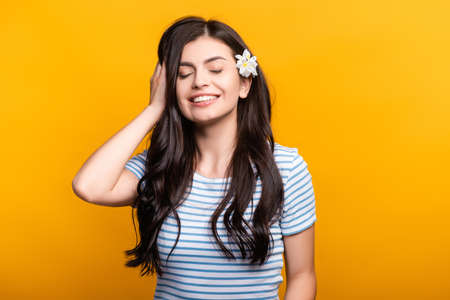 brunette young woman with flowers in hair and closed eyes smiling isolated on yellow Stock fotó - 154911338
