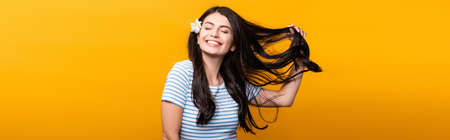 brunette young woman with flowers in hair and closed eyes smiling isolated on yellow, panoramic shot Stock fotó - 154911347