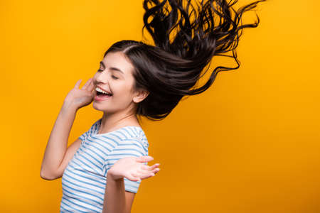 brunette long haired woman with curls jumping isolated on yellow Stock fotó