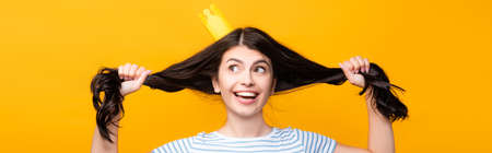 brunette woman in paper crown holding hair and smiling isolated on yellow, panoramic shot Stock fotó - 154911378