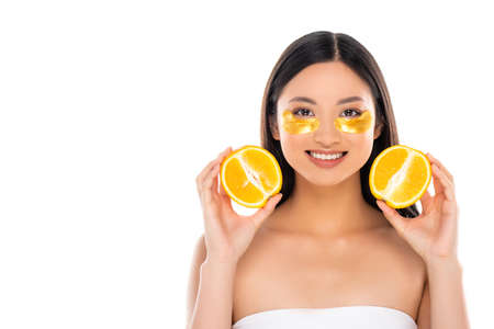 young asian woman with golden eye patches on face holding halves of fresh orange isolated on white