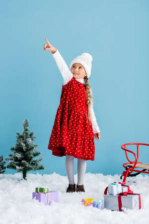 kid in hat and winter outfit standing on snow and pointing with finger while looking up near presents and sleigh isolated on blue