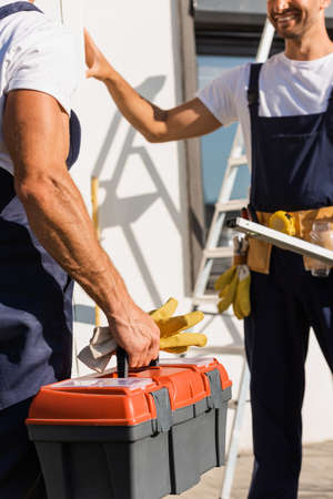 Cropped view of builder holding gloves and toolbox near colleague outdoors Stockfoto