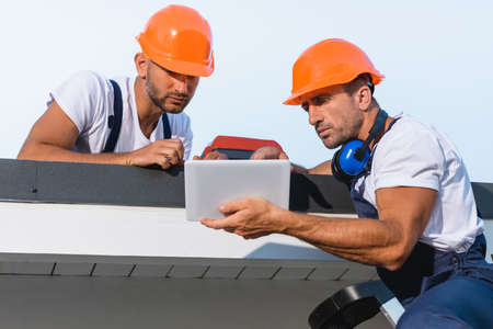 Selective focus of handymen in workwear using digital tablet while working on roof of building