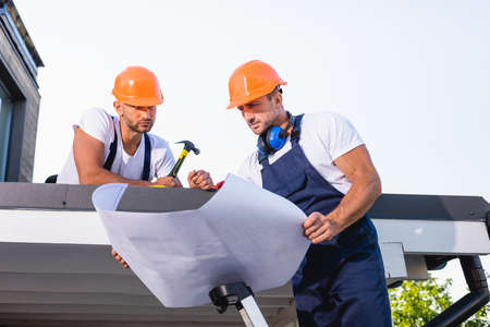 Handyman holding blueprint while standing on ladder near colleague with hammer on roof of building