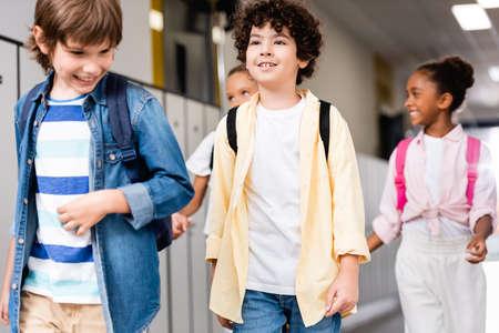 excited multicultural schoolchildren walking along school corridor