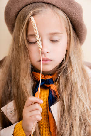 fashionable blonde girl with closed eyes in autumn outfit holding wheat spike 스톡 콘텐츠 - 155341507