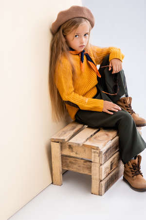 fashionable blonde girl in autumn outfit with sunglasses sitting on wooden box on beige and white background Foto de archivo