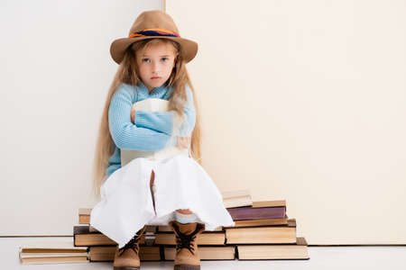 sad fashionable blonde girl in brown hat and boots, white skirt and blue sweater sitting with book near beige wall