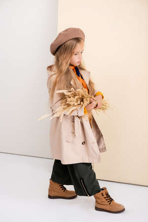 side view of fashionable blonde girl in autumn outfit walking with wheat spikes on beige and white background