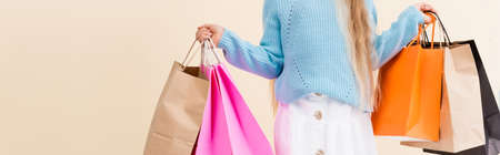 cropped view of girl in white skirt and blue sweater with colorful shopping bags isolated on beige, panoramic shot