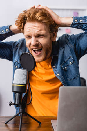 angry announcer touching head while screaming in microphone at workplace Stock Photo