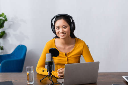 joyful asian announcer in wireless headphones looking at camera while sitting near laptop and microphone Stock Photo