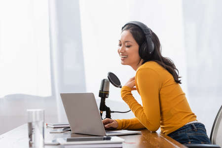 laughing asian radio host in wireless headphones touching chest while working near microphone and laptop