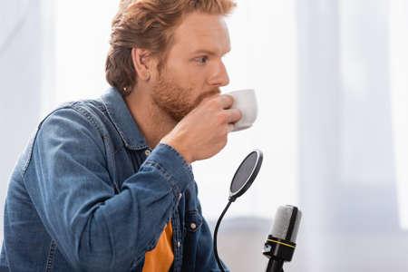 young redhead radio host in denim shirt drinking coffee near microphone