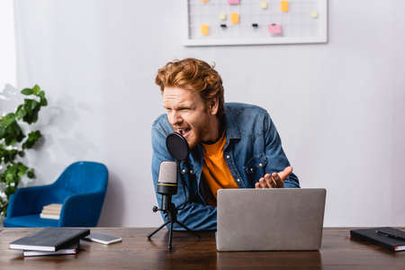 angry redhead announcer gesturing while screaming in microphone near laptop