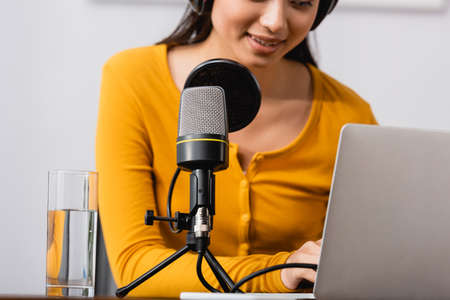 partial view of asian announcer typing on laptop near microphone in radio studio