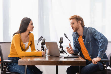 redhead broadcaster talking to asian woman near microphones and laptop in radio studio