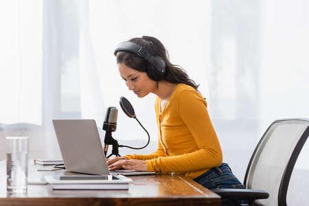 brunette asian announcer in wireless headphones typing on laptop near microphone in studio